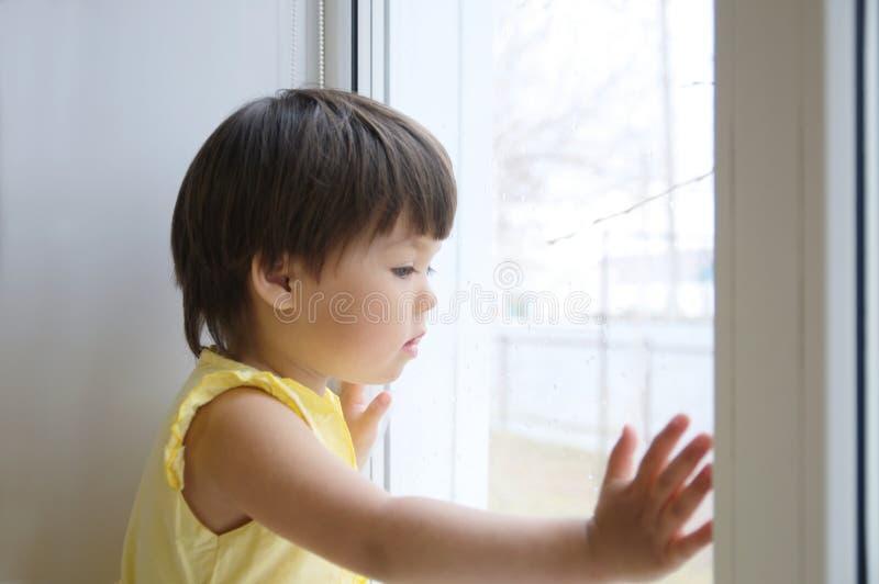 Mała dziewczynka przyglądająca out nadokienny upragnienie dla niektóre światła słonecznego dziecka obsiadania dom przy deszczowym fotografia royalty free