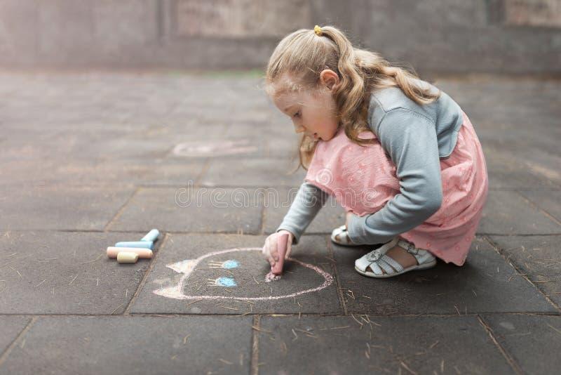 Mała dziewczynka remisów kreda na asfalcie zdjęcie royalty free