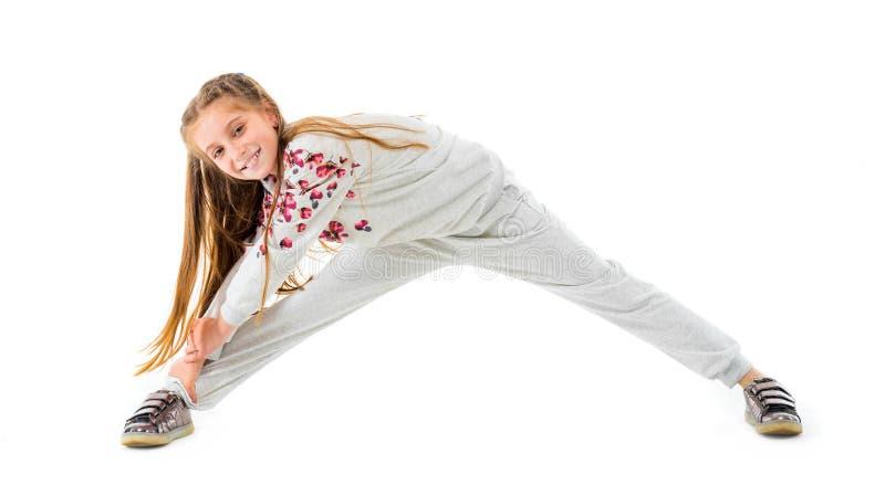Mała dziewczynka robi rozciąganiu odizolowywającemu na białym tle zdjęcia royalty free