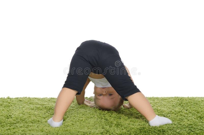 Mała dziewczynka robi skłonom na dywanie zdjęcie royalty free