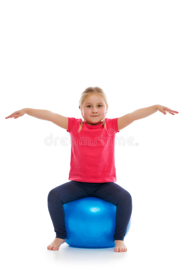 Mała dziewczynka robi sprawności fizycznej ćwiczeniu z gym piłką. fotografia stock