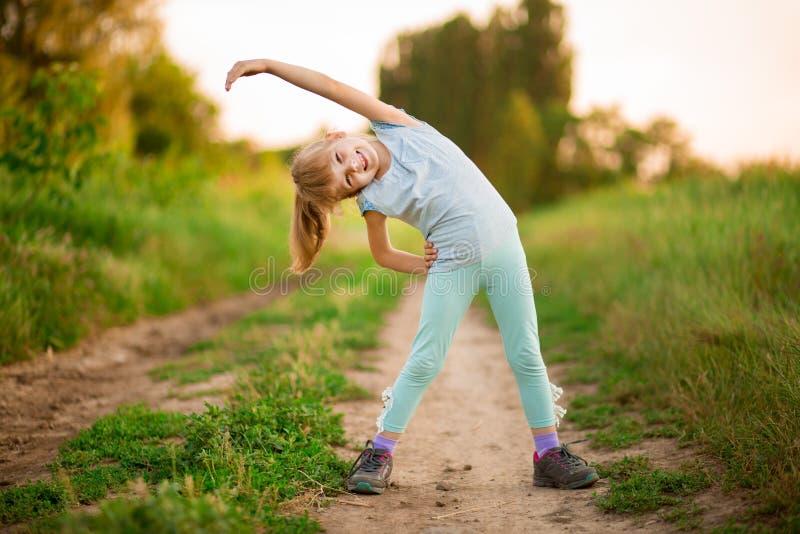 Mała dziewczynka robi sprawności fizycznej ćwiczy plenerowego obrazy stock
