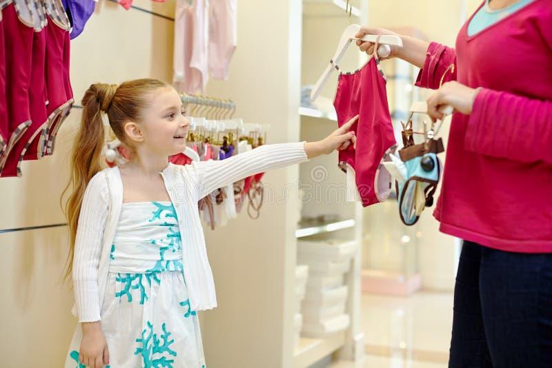 Mała dziewczynka robi wyborowi między dwa swimsuits obrazy stock