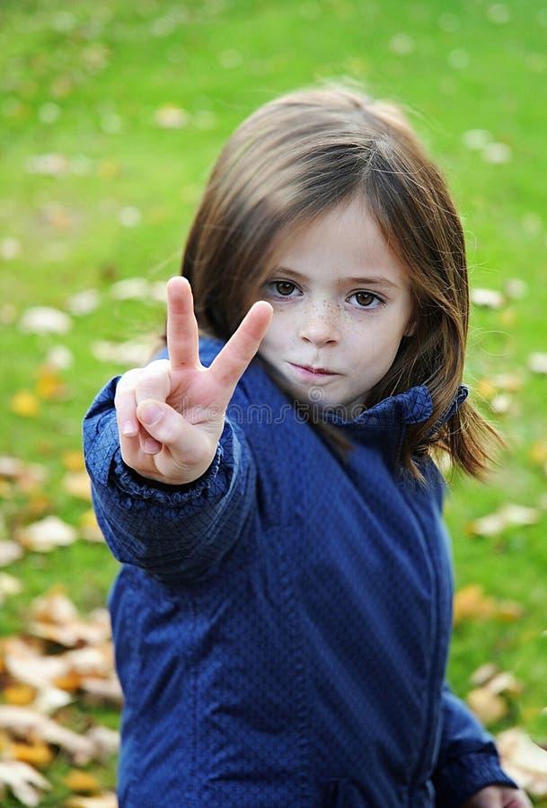 Mała dziewczynka robi zwycięstwo znakowi obraz stock
