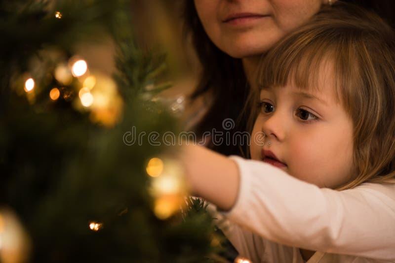 Mała dziewczynka ruchliwie w dekorować choinki obraz stock