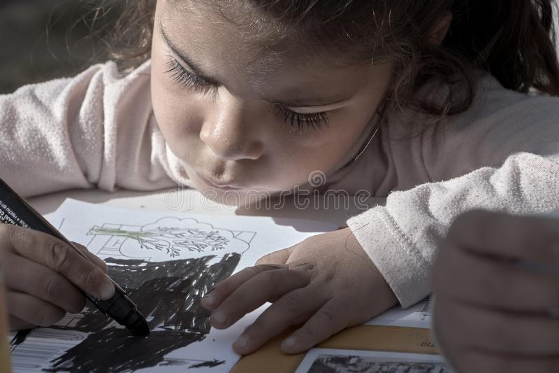 Mała dziewczynka rysuje na odświętności dziecka ` s dniu w parku w Trinidad, obrazy stock