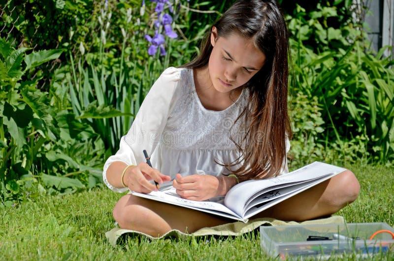 Mała Dziewczynka rysunek w ogródzie fotografia royalty free