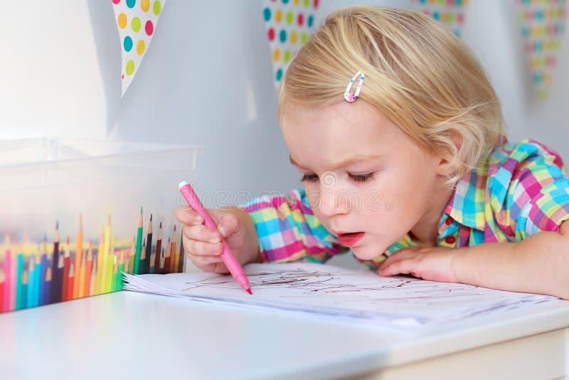 Mała dziewczynka rysunek z kolorowymi ołówkami obrazy stock