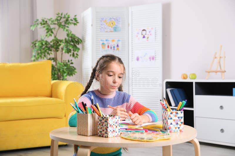Mała dziewczynka rysunku obrazek przy stołem z obrazów narzędziami obrazy stock