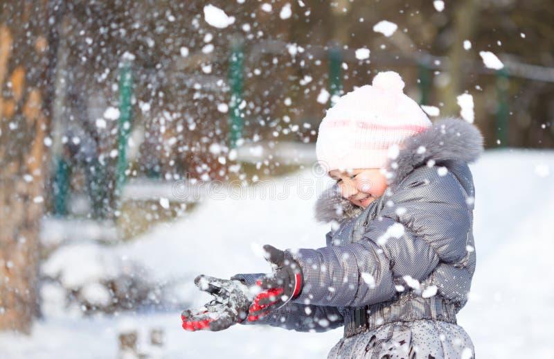 Mała dziewczynka rzuca śnieg obraz stock