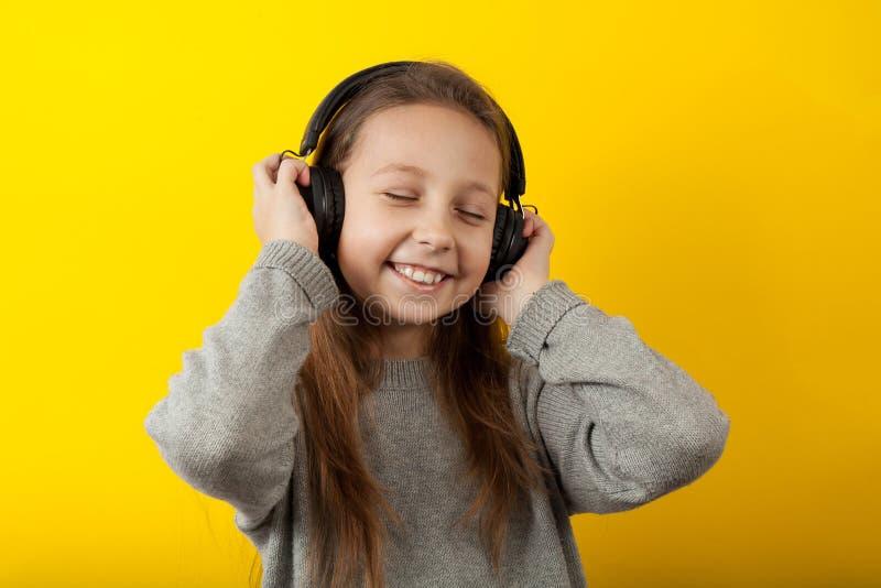 Mała dziewczynka słucha muzyki w słuchawkach z zamkniętymi oczami i uśmiechniętym, zamkniętym portretem na żółtym tle fotografia royalty free