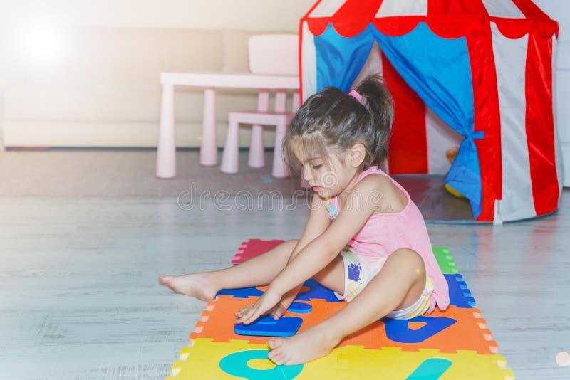 Mała dziewczynka siedzi kolorową łamigłówki sztuki matę i trzyma fotografia stock