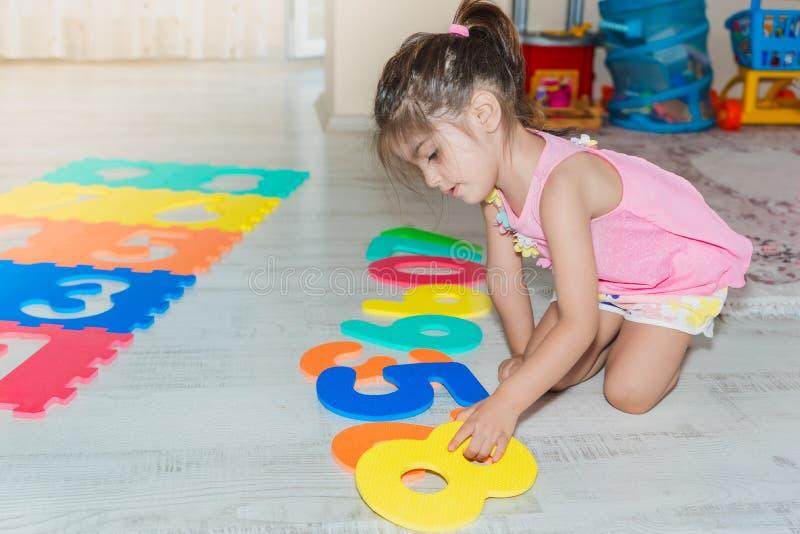 Mała dziewczynka siedzi kolorową łamigłówki sztuki matę i trzyma zdjęcia royalty free