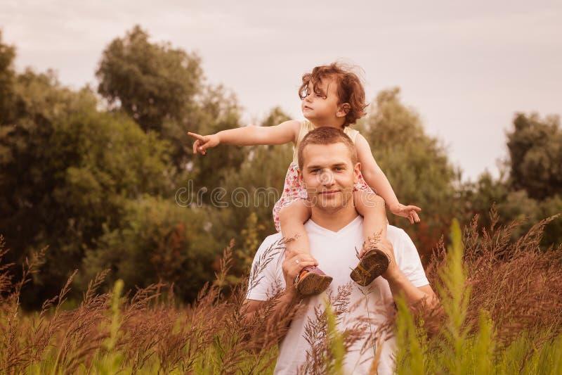 Mała dziewczynka siedzi na jej ojca ` s ramionach w lecie w parku fotografia royalty free