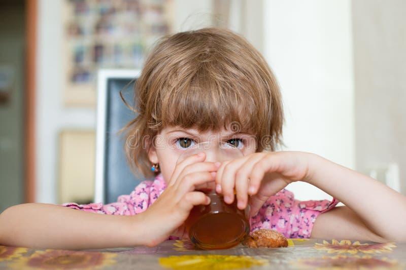 Mała dziewczynka siedzi przy stołową pije herbatą od przejrzystego szkła obraz royalty free
