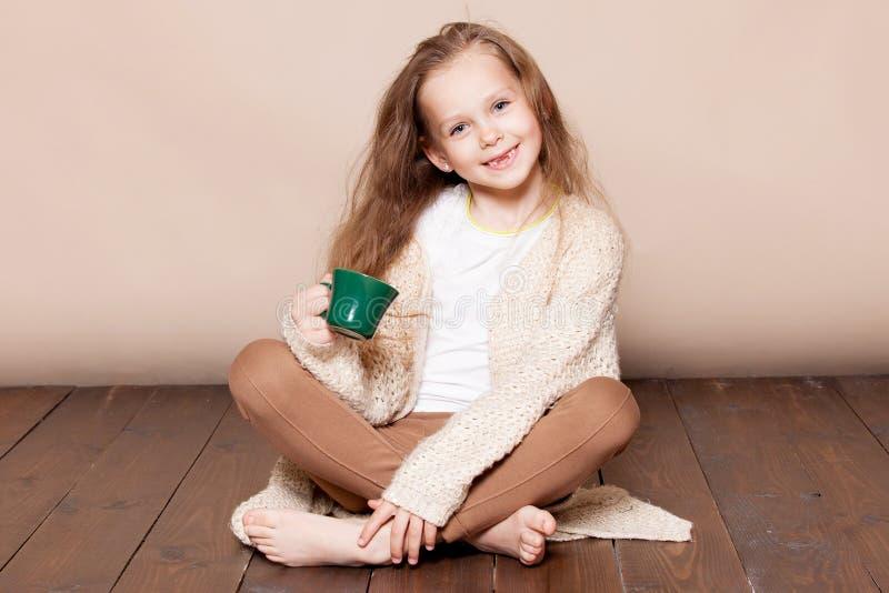 Mała dziewczynka siedzi z kubkiem na podłoga zdjęcia stock
