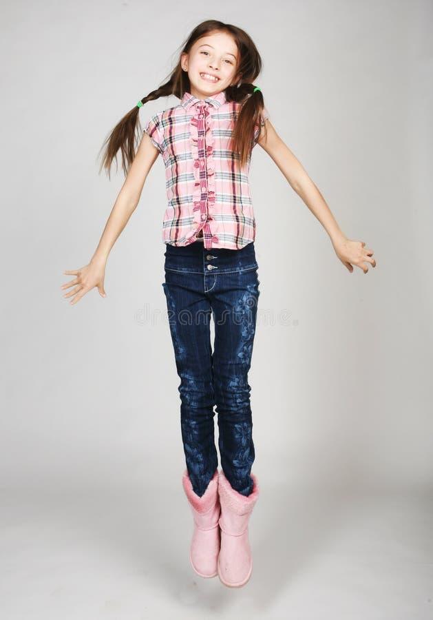 mała dziewczynka skacze na szarym tle obrazy royalty free