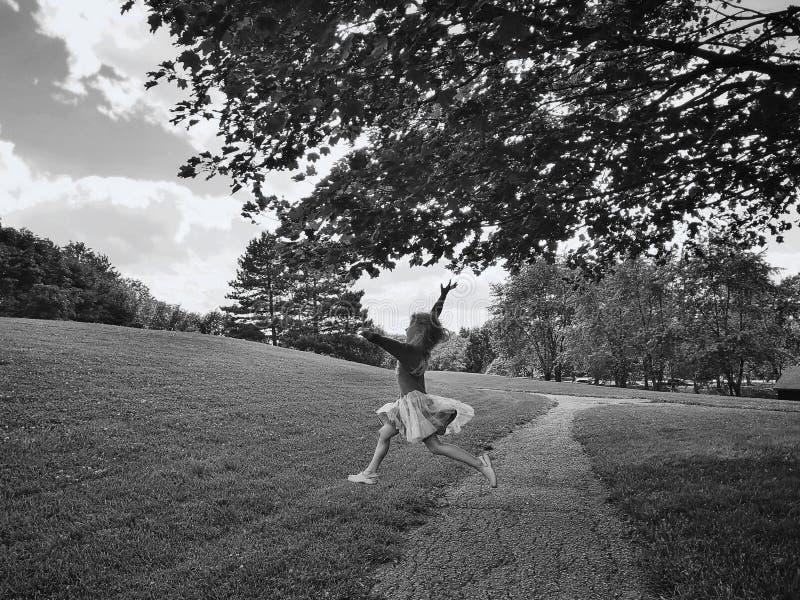 mała dziewczynka skakająca w parku na wakacje Czarno-biały portret śmiesznego uśmiechniętego dziecka fotografia royalty free
