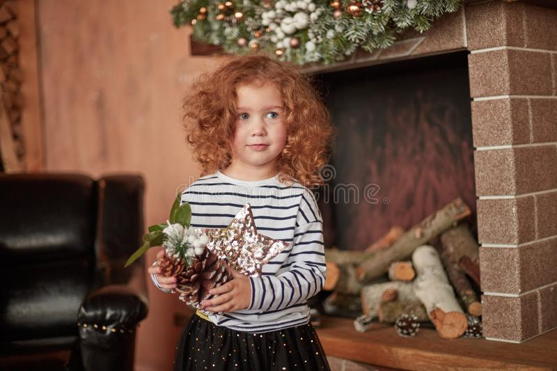 Mała dziewczynka stoi bezczynnie grabę na wigilii z sosnowym rożkiem obraz royalty free