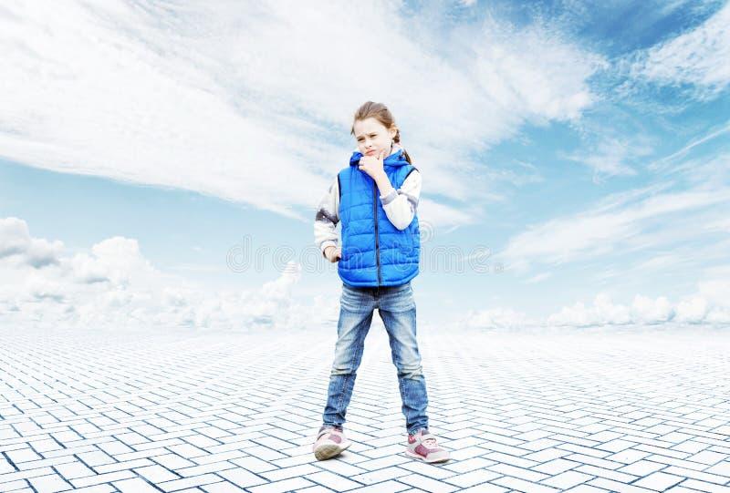 Mała dziewczynka stojaki w zadumie po środku otwartej przestrzeni obraz stock