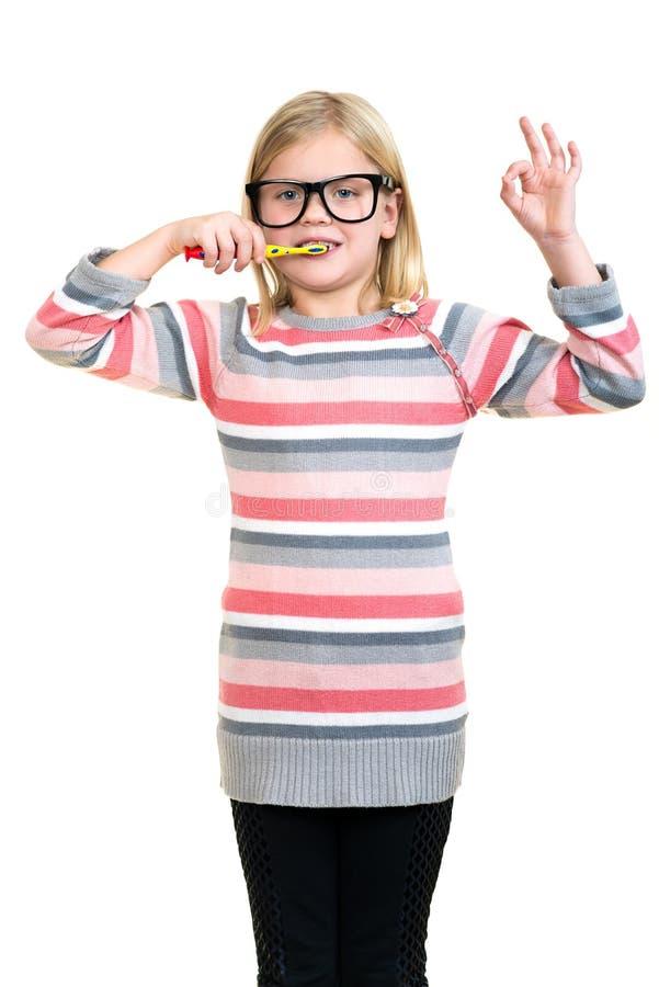 Mała dziewczynka szczotkuje jej zęby odizolowywających na białym tle fotografia stock