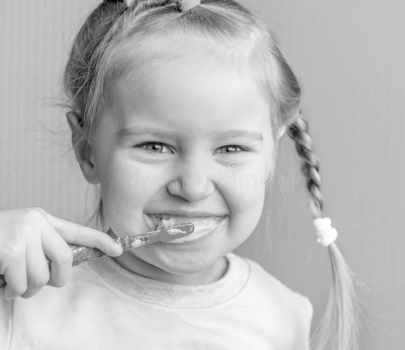 Mała dziewczynka szczotkuje jej zęby, ono uśmiecha się obraz stock