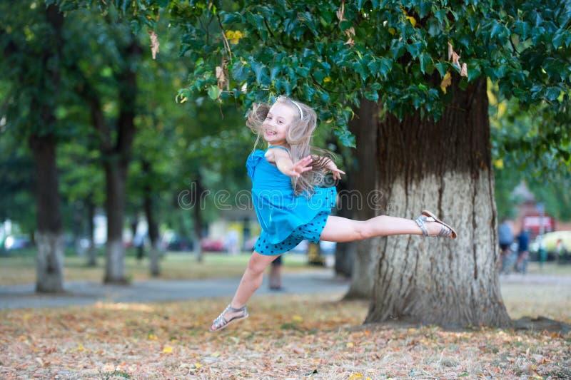 Mała dziewczynka tancerz skacze w lato parku obraz stock