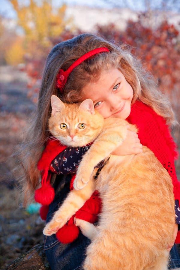 Mała dziewczynka trzyma dużego czerwonego kota obraz stock