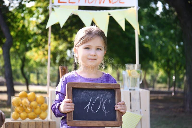 Mała dziewczynka trzyma małego blackboard z ceną blisko lemoniada stojaka w parku fotografia royalty free