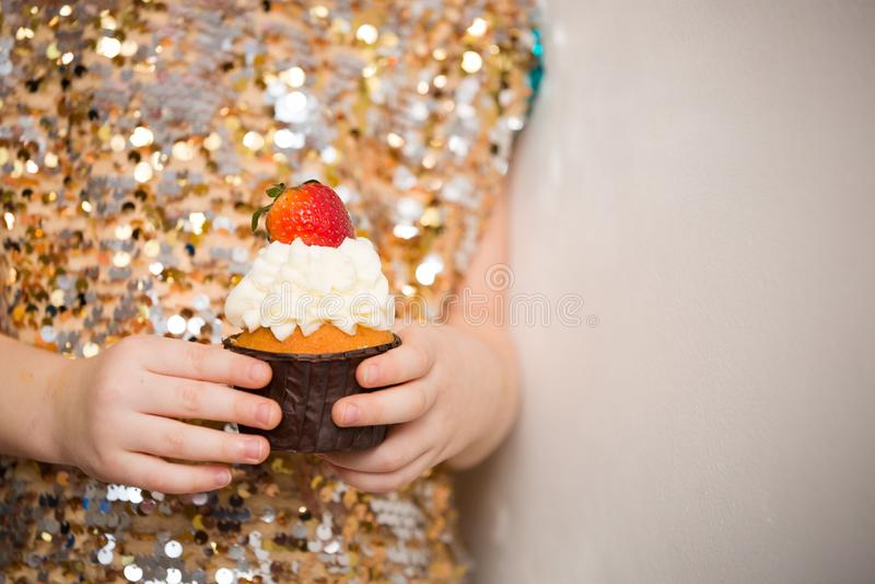 Mała dziewczynka trzyma piękną babeczkę w błyszczenie sukni, zakończenie w górę Piekarnia, s?odki jedzenie i ludzie poj??, zdjęcie stock