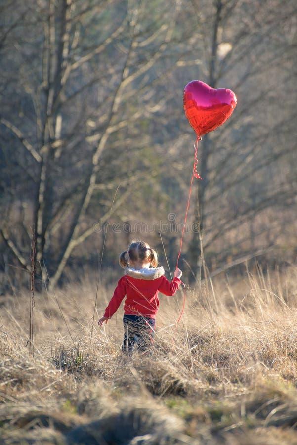 Mała dziewczynka trzyma sercowatego balon obrazy stock