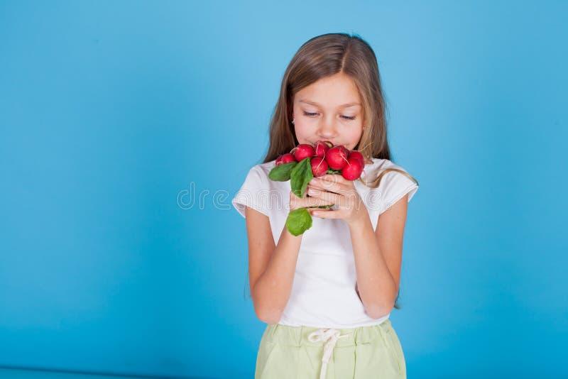Mała dziewczynka trzymający czerwonych rzodkwi zdrowych karmowych warzywa zdjęcia stock