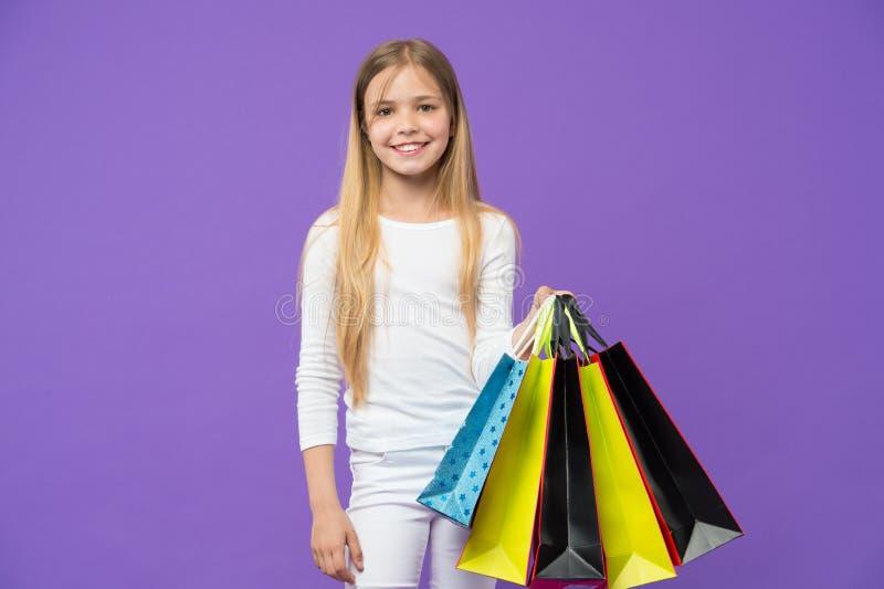 Mała dziewczynka uśmiech z torba na zakupy na fiołkowym tle Szczęśliwy dziecko z papierowymi torbami na purpurowym tle Dzieciaka  fotografia stock