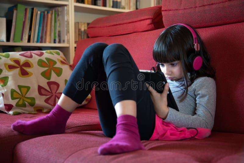 Mała dziewczynka używa pastylka komputer osobistego obraz royalty free
