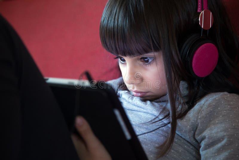 Mała dziewczynka używa pastylka komputer osobistego zdjęcia stock