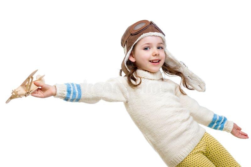 Mała dziewczynka ubierał jak pilot bawić się z drewnianym samolotem fotografia stock