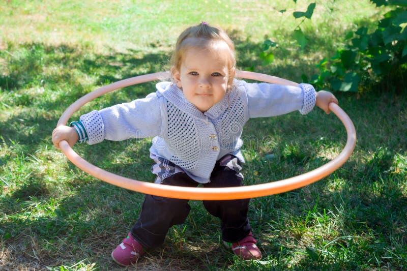 Mała dziewczynka uczy się rozdawać z hulahup Dziecko trzyma obręcz z dwa rękami obraz royalty free