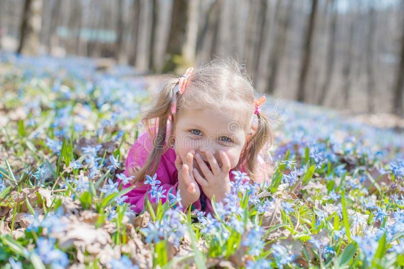 Mała dziewczynka wącha kwiaty podczas gdy siedzący na zielonej łące zdjęcia stock