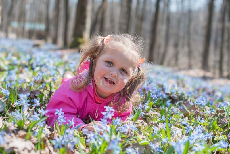 Mała dziewczynka wącha kwiaty podczas gdy siedzący na zielonej łące obraz stock