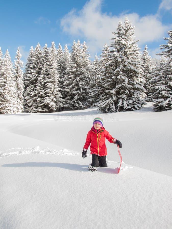 Mała dziewczynka w śniegu z saneczki fotografia royalty free