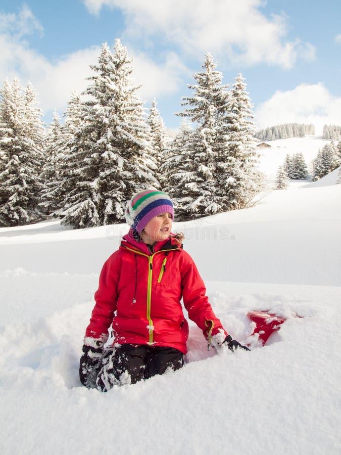 Mała dziewczynka w śniegu z saneczki zdjęcie stock