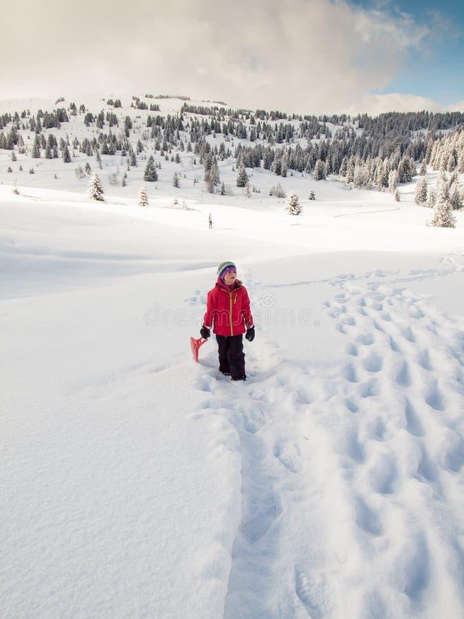 Mała dziewczynka w śniegu z saneczki obraz stock