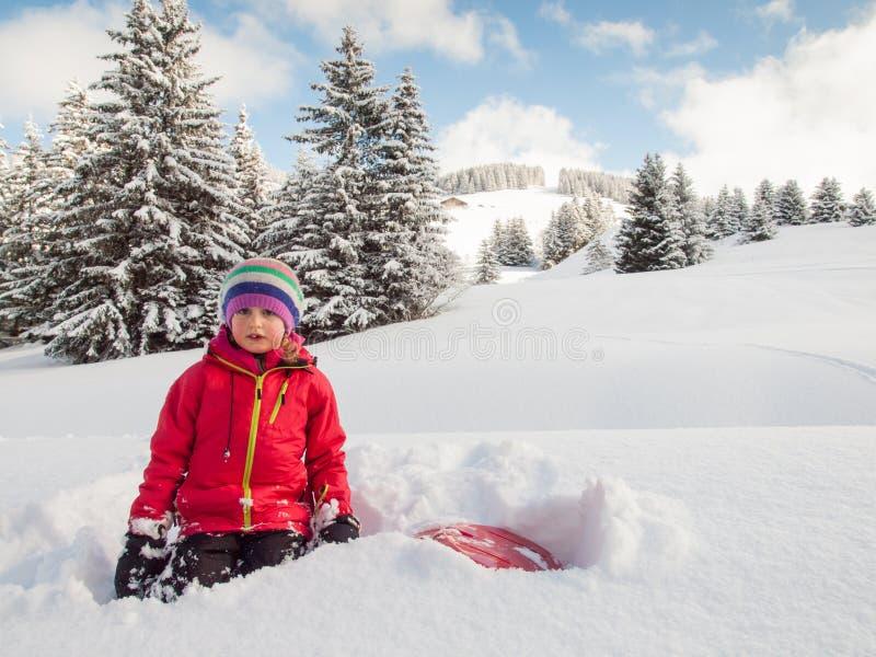 Mała dziewczynka w śniegu z saneczki zdjęcie royalty free