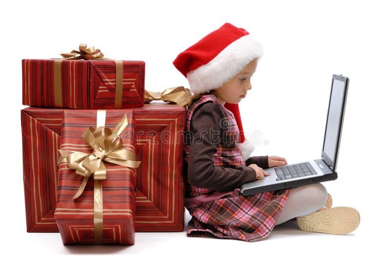 Mała dziewczynka w Święty Mikołaj nakrętce z boże narodzenie prezentem i laptopem zdjęcie stock