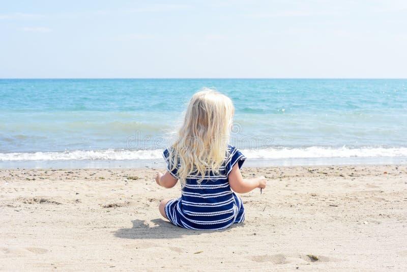 Mała dziewczynka w błękit sukni obsiadaniu na plaży cieszy się beauti obrazy royalty free