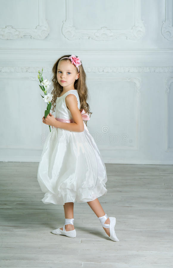 Mała dziewczynka w bielu kwiacie i sukni pozuje w pięknym s fotografia stock