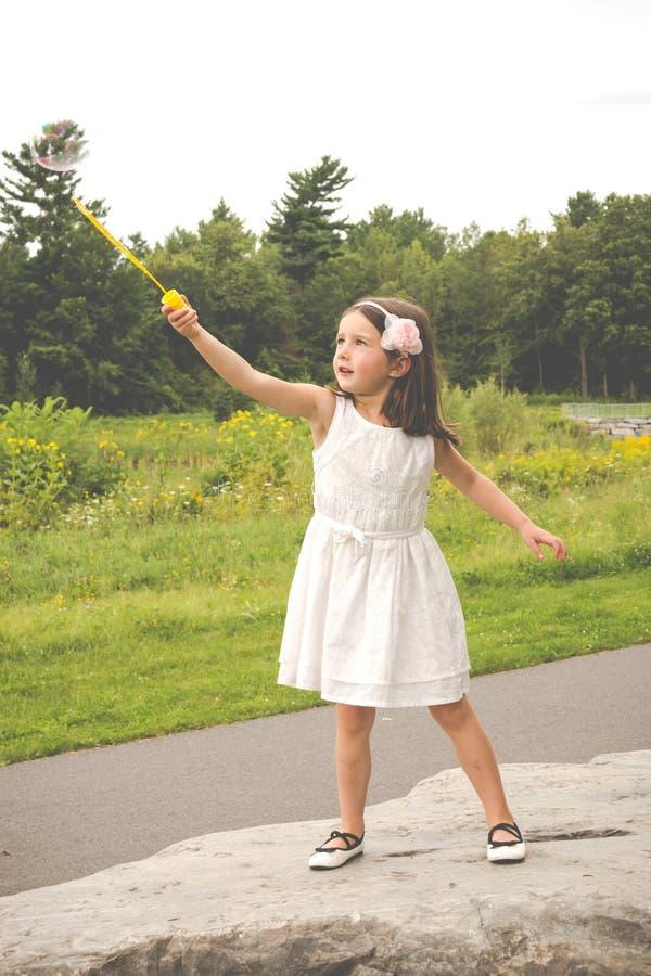 Mała dziewczynka w bielu smokingowy bawić się z bąbla producentem w parku zdjęcia royalty free