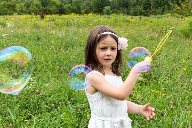 Mała dziewczynka w bielu smokingowy bawić się z bąbla producentem w parku zdjęcia stock