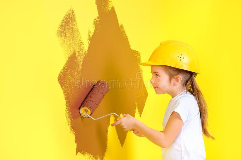 Mała dziewczynka w budowa hełmie maluje ścianę z rolownikiem zdjęcia stock