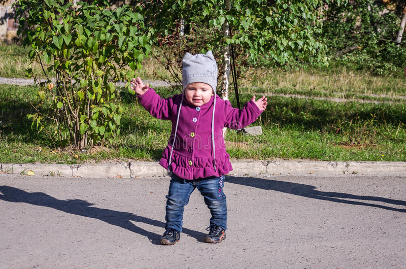 Mała dziewczynka w cajg kurtce i kapeluszowym robi uczenie chodzić jego pierwszych kroki na gazonie w zielonej trawie zdjęcia stock